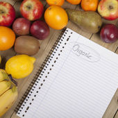 Fruits and book on wooden surface — Stock Photo