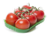 Fresh tomatoes isolated on white background in green tray — Stock Photo