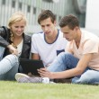 Three students look at an Ipad — Stock Photo #50199983