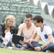 Three students look at an Ipad — Stock Photo #50199991