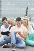 Four students sitting on the ground — Stock Photo