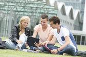 Three students look at an Ipad — Stock Photo