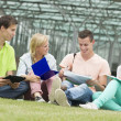 Four students learning while sitting on the ground — Stock Photo #50200019