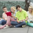 Four students learning while sitting on the ground — Stock Photo #50200023