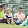 Four students learning while sitting on the ground — Stock Photo #50200029