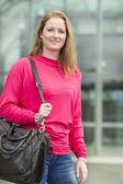 Ung student leende med hennes väska i hennes händer — Stockfoto