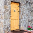 Wooden door  on stone wall. — Stock Photo