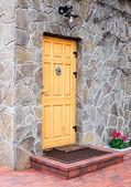 Wooden door on stone wall. — Stock Photo