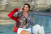 Woman sits near the fountain and talking on the phone — Stok fotoğraf