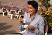 Attractive business woman drinking coffee in a street cafe — Stock Photo