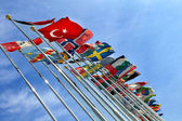 Different countries flags united together against blue sky — Stock Photo