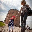 Mother and baby walking in old city - Stock Photo