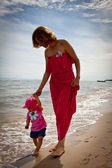 Mother with her baby having fun on the beach — Stock Photo