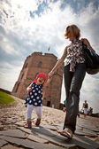 Mother and baby walking in old city — Stock Photo