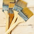 Old paint brushes on wooden background — Stock Photo #15642063