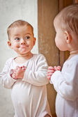 Baby standing against the mirror — Stock Photo