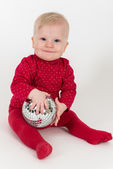 Sitting smiling baby in red with party ball — Stock Photo