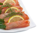 Close-up of plate with smoked salmon on white background. — Stock Photo