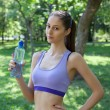 Girl drinks water from a bottle after running — Stock Photo #48840105