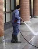 Is het reinigen van een man met een hogedruk reiniger — Stockfoto