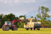 Tractor lifting hay bale on barrow — Stock Photo