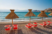 Sunshades and orange deck chairs on beach at Baska - Krk - Croat — Stock Photo