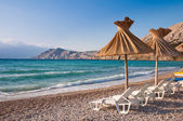 Sunshade and deck chair on beach at Baska in Krk - Croatia — Stock Photo