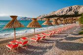 Sombrillas y reposeras naranjas en playa de baska - krk - croata — Foto de Stock