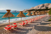 Sunshades and orange deck chairs on beach at Baska - Krk - Croat — Foto de Stock