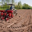 Old tractor with red sower working fields wide angle — Stock Photo
