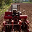 Old tractor with sower parked on worked field upside view — Stock Photo