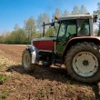 Red and white tractor with vibrocultor ready to work fields side — Stock Photo