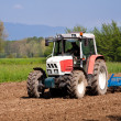 Stock Photo: Red and white tractor with vibrocultor working fields front side