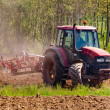 Red tractor with vibrocultor on fields background trees — Stock Photo