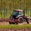 Red tractor with vibrocultor on fields side back view — Stock Photo