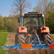 Tractor with vibrocultor working fields back view close — Stock Photo