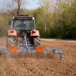Stock Photo: Tractor with vibrocultor working fields back view
