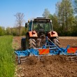 Tractor with vibrocultor working fields back view — Stock Photo