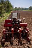 Viejo tractor con sembrador estacionado en campo trabajado al revés vista — Foto de Stock