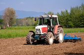 Red and white tractor with vibrocultor working fields front side — Stock Photo