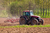 Red tractor with vibrocultor on fields side view — Stock Photo