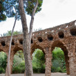 Stock Photo: Viaducto arcs and trees in Park Guell at Barcelona