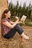 Beautiful woman is reading a book outdoor in a field — Stock Photo