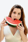 Cute woman bites into a slice of watermelon — Stock Photo