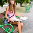 Beautiful young student girl studying outdoors. - Stock fotografie