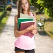 Beautiful young student girl outdoors holding exercise books. - Stockfoto