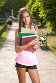 Beautiful young student girl outdoors holding exercise books. — Stock Photo