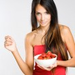 Slender young brunette holdng strawberries. — Stock Photo #13624773