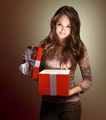 Hermosa morena de espiar dentro de caja de regalo. — Foto de Stock