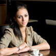 Lonely brunette in a coffee shop. — Stock Photo